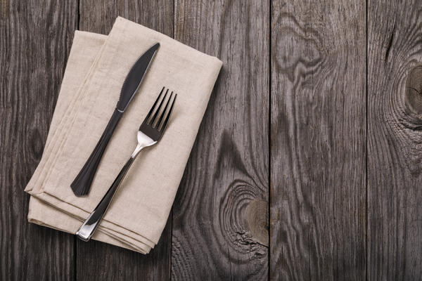 Cutlery and napkin on a wooden table with copy space, top view. Food background